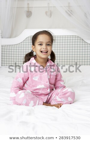 Young girl sitting on the bed wearing a pyjama  Stock photo © wavebreak_media
