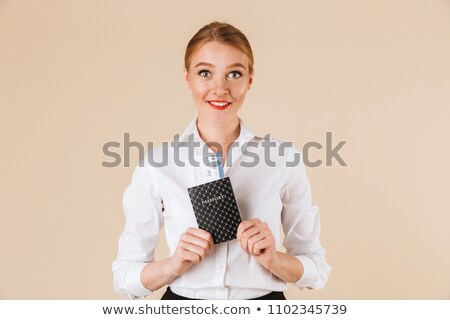 Portrait of confident young business woman holding passport Stock photo © HASLOO