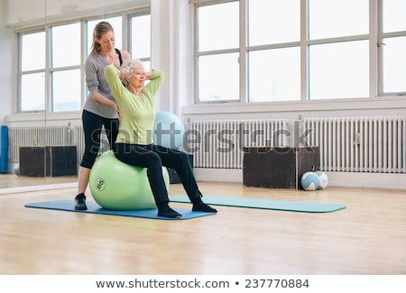 Woman being helped by her personal trainer Stock photo © photography33