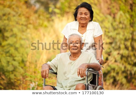 Senior woman pushing her disabled hasband on wheelchair Stock photo © Witthaya