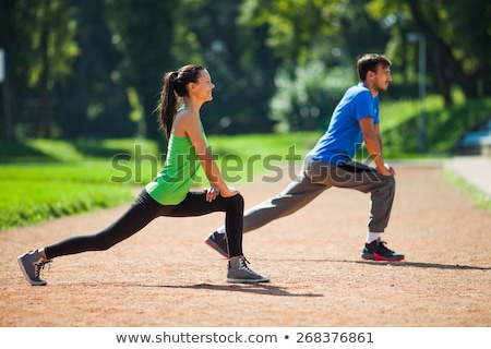 Smiling athletic young woman warming up for exercise by stretching stock photo © darrinhenry