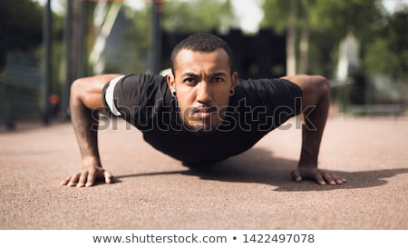 Stock photo: Handsome Athletic Young Man with Tattoo Looking Up
