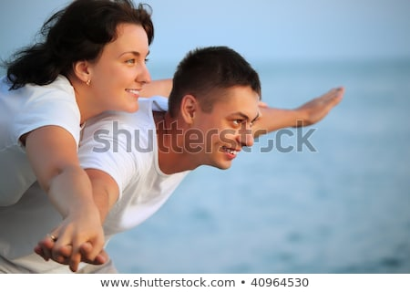 Smiling man and young woman placed hands in sides against sea Stock photo © Paha_L