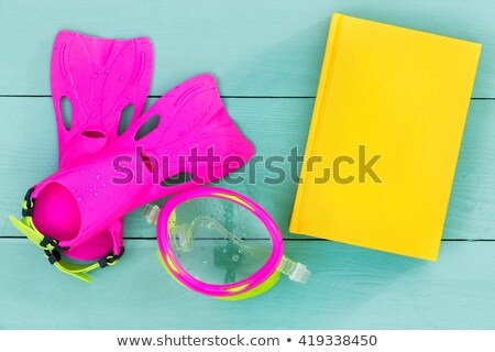 Bright flippers, goggles and book on a green table Stock photo © ozgur