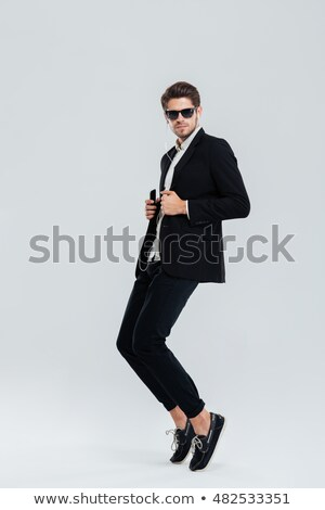 Serious businessman listening music with earphonea and standing on tiptoe Stock photo © deandrobot
