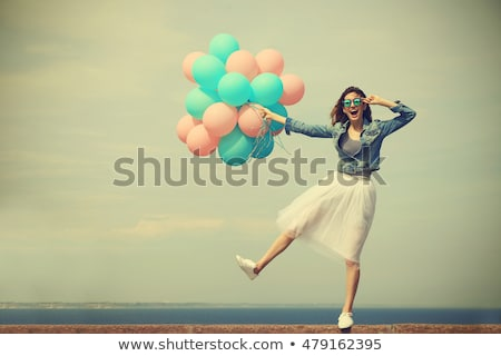 Happy young woman having fun with colorful latex balloons Stock photo © deandrobot