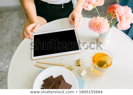 Woman holding tea cup and blank screen tablet at home Stock photo © deandrobot