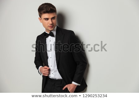 relaxed man in tuxedo and bowtie looking down stock photo © feedough