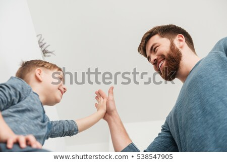 Father with his son give high five to each other Stock photo © deandrobot