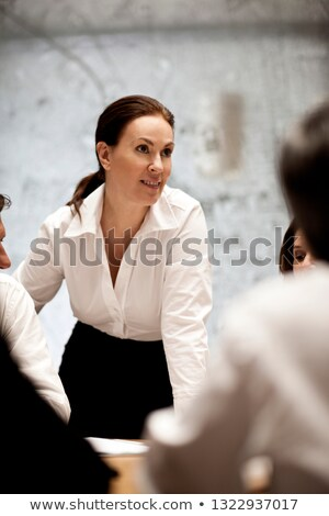 Vertical picture of woman sitting by the table Stock photo © deandrobot