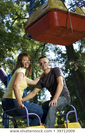 Stock photo: adult man and woman on a carousel