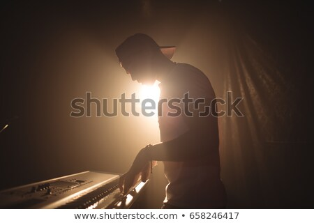 Side view of musician playing piano in illuminated nightclub Stock photo © wavebreak_media