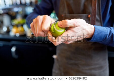 bartender removing peel from lime at bar Stock photo © dolgachov