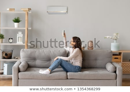 Woman Adjusting Air Conditioner With Remote Control Stock photo © AndreyPopov