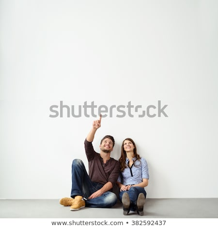 Stock photo: happy young couple pointing fingers together