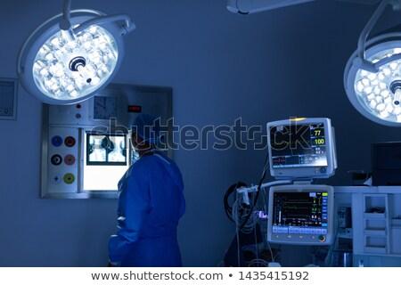 Male surgeon looking at machine in operation theater Stock photo © wavebreak_media