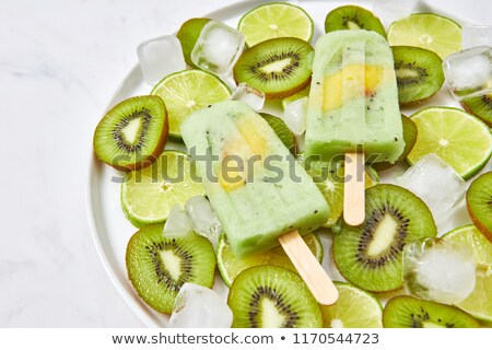 Vanilla popsicle with peach piece as a summer dessert on a marble background. Top view. Frozen fruit Stock photo © artjazz
