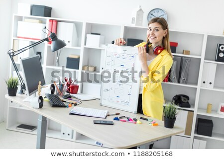 a young girl stands near a table and holds a marker and a magnetic board in her hands on the neck stock photo © traimak