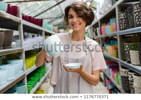 Stock photo: Woman Gardener Standing In Greenhouse Choosing Vase Pot For Plants