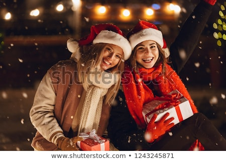 happy young friends sitting outdoors in evening in christmas hats holding gift box stock photo © deandrobot
