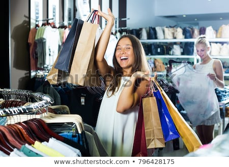 consumerism woman holding many shopping bags in fashion boutique Stock photo © snowing