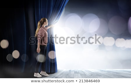 woman open blue curtains of the theater stage stock photo © alphaspirit