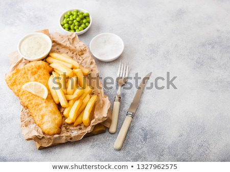 traditional british fish and chips with tartar sauce on chopping board on white stone table backgrou stock photo © denismart