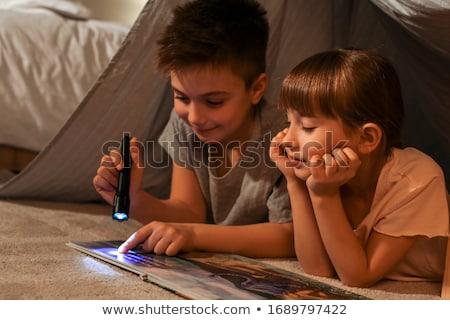 Portrait of brother and sister reading an interesting story Stock photo © konradbak