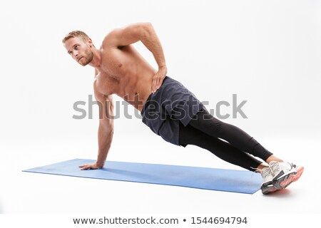 Portrait of a confident sportsman doing plank exercise Stock photo © deandrobot