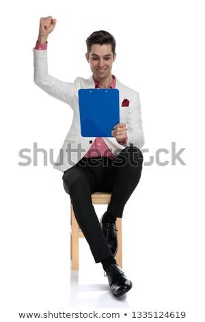 seated elgant man reading on clipboard good news and celebrates  Stock photo © feedough