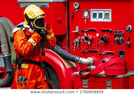 Fire fighter getting on fire engine Stock photo © Kzenon