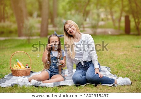 Two Young Girls Blowing Bubbles On Countryside Picnic Stock photo © monkey_business