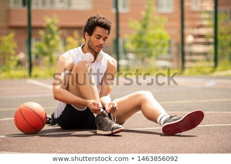 Stock photo: Young athlete sitting on basketball court and tying shoelace of sneaker