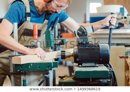 Carpenter making stairway drilling holes in stair rail Stock photo © Kzenon
