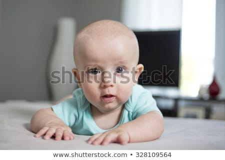 Four month old baby boy is laying on her tummy at home Stock photo © Lopolo