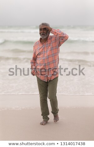 Front view of senior man with shielding eyes and hand in pocket walking on the beach Stock photo © wavebreak_media