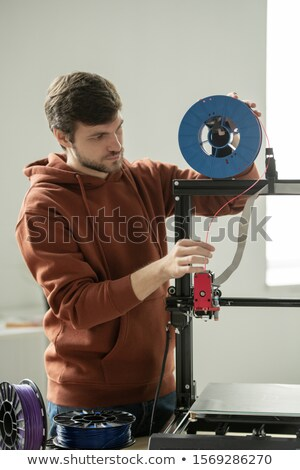 Young man in casualwear putting red filament into printhead of 3d printer Stock photo © pressmaster