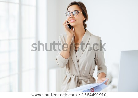 Happy thoughtful successful female employee holds modern cellphone near ear, has telephone conversat Stock photo © vkstudio