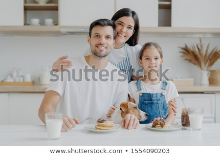 Happy family and dog pose in cozy kitchen, eat fresh homemade pancakes with chocolate and milk, look Stock photo © vkstudio