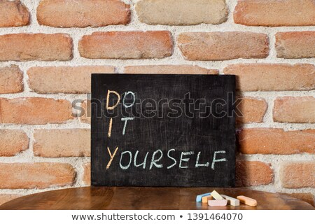 Black chalkboard with the phrase DO IT YOURSELF drown by hand on Stock photo © marylooo