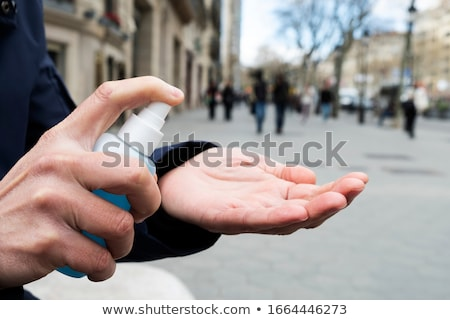 man on the street disinfecting his hands Stock photo © nito