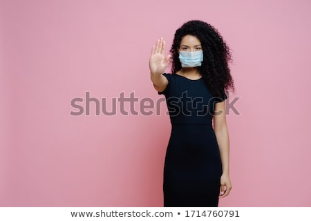Covid 19 outbreak, viral disease. Photo of ethnic woman with curly hair makes stop gesture with palm Stock photo © vkstudio