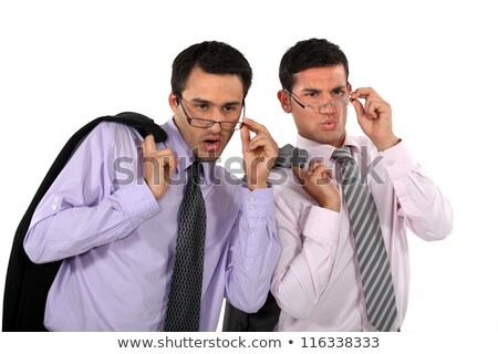 Surprised man peers into spectacles
