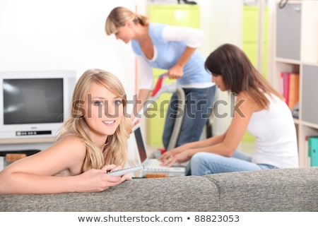 a woman watching tv, a woman doing computer and another one vacuuming Stock photo © photography33