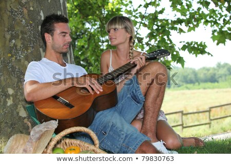 Young couple with picnic basket sat by tree Stock photo © photography33