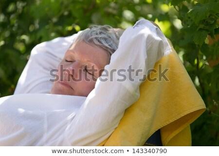 Mature woman sleeping on lounger Stock photo © doupix
