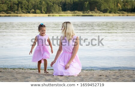 Beautiful blonde girl walking near the sea Stock photo © konradbak