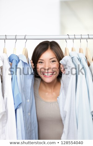 Young woman at clothes shop peeping through clothes Stock photo © HASLOO