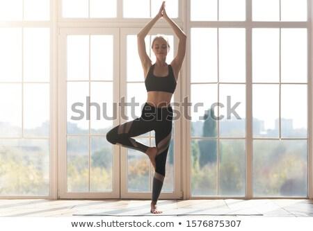 woman doing stretching yoga exercises stock photo © hasloo
