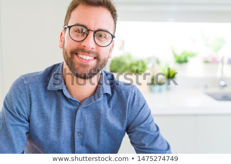 Young Man Wearing Glasses Looking Out of a Window  Stock photo © NicoletaIonescu